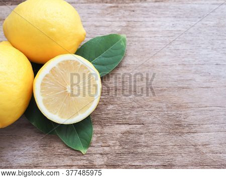 Half And Group Of Fresh Lemon With Leaves On Wooden Background With Copy Space. High Vitamin C, Whic