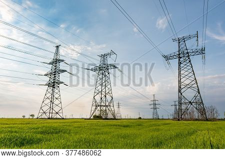 High Voltage Lines And Pylons And A Green Agricultural Landscape On A Sunny Day. Association Of Agri