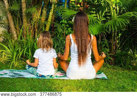 Mum And Daughter Practicing Yoga Together In The Garden. Outdoor Yoga And Meditation Practice. Famil