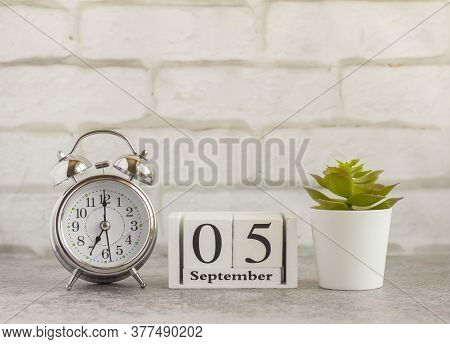 September 5 On A Wooden Calendar Next To The Alarm Clock.september Day, Empty Space For Text.calenda
