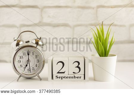 September 23 On A Wooden Calendar On A Table Or Shelf Next To An Alarm Clock.one Day Of The Autumn M