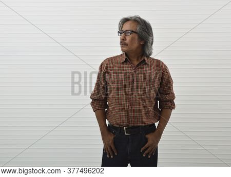 Confident Senior Man In Red Casual Shirt, Blue Jeans And Eyeglasses Standing Over White Wall Backgro
