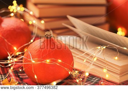 Autumn Books.autumn Cozy Reading.stack Of Books, Red Hokkaido Pumpkins With Glowing Garland, Checker