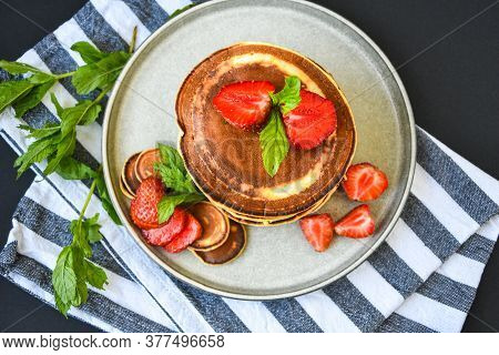 Plate With Traditional Pancakes And Tiny Pancake Cereal With Strawberries And Mint Leaves On A Dark