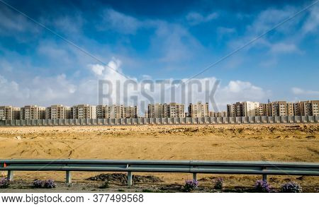 Panorama view of a fenced part of desert city  with tall buildings on the road to Cairo, Egipt.