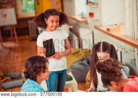 Girl Showing A Video On Her Tablet To Her Classmates