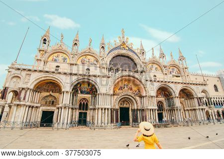 Woman In Yellow Sundress With Straw Hat Walking To Saint Mark Basilica
