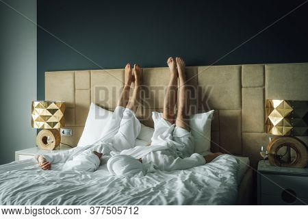 Young Couple Of Man And Woman In White Bath Robes And Towels On Their Heads Are Lying In Bed. Newly