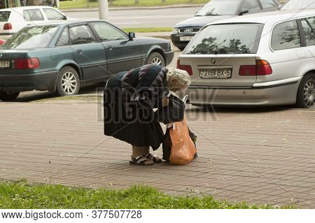 The Poor Old Woman Bent Over Her Shopping Bags In The Middle Of The Summer City Sidewalk. Minsk, Bel