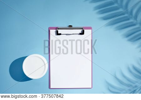 Blank Cosmetics Jar And Empty Clipboard With Palm Shadows On Blue Background. Moisturizing Cream Jar