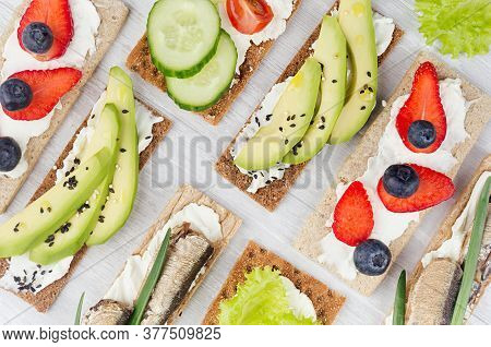 Summer Light Sweet Open Sandwiches On Crisps Bread With Vegetables, Ripe Fruits, Fish Preserves, Cre