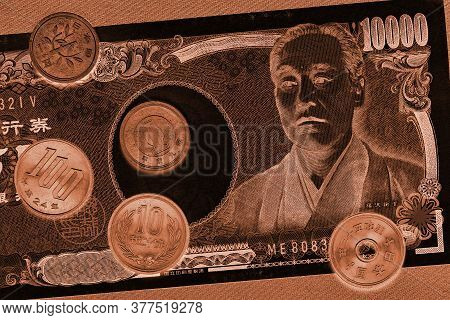 Japanese Money: A Bill Of 10,000 And Coins Of 100, 10 And 1 Yen Close-up. Dark Inverted Black And Br
