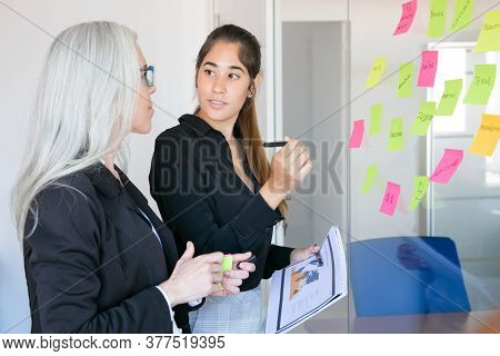 Young Latin Employer Holding Pen And Statistic Documents And Looking At Boss. Focused Confident Grey