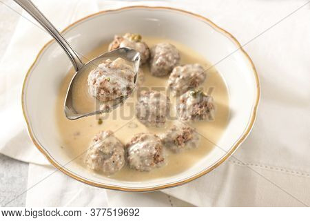 Ladle Is Liftiting A Meatball From A Bowl With Koenigsberger Klops, Which Are Boiled Beef Balls In A
