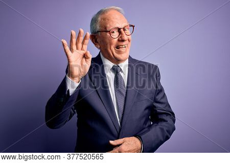 Grey haired senior business man wearing glasses and elegant suit and tie over purple background Waiving saying hello happy and smiling, friendly welcome gesture