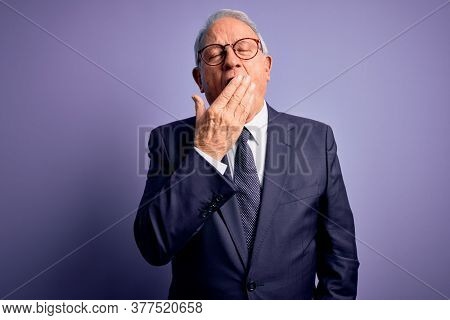 Grey haired senior business man wearing glasses and elegant suit and tie over purple background bored yawning tired covering mouth with hand. Restless and sleepiness.