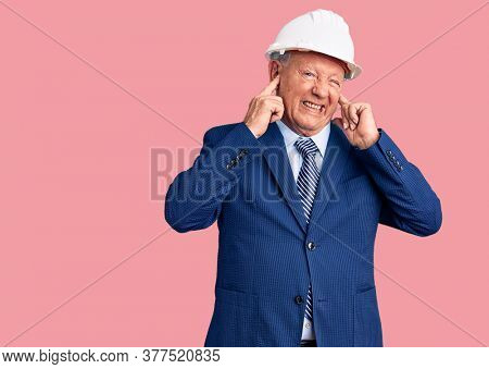 Senior handsome grey-haired man wearing suit and architect hardhat covering ears with fingers with annoyed expression for the noise of loud music. deaf concept.