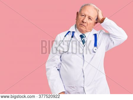 Senior handsome grey-haired man wearing doctor coat and stethoscope confuse and wondering about question. uncertain with doubt, thinking with hand on head. pensive concept.