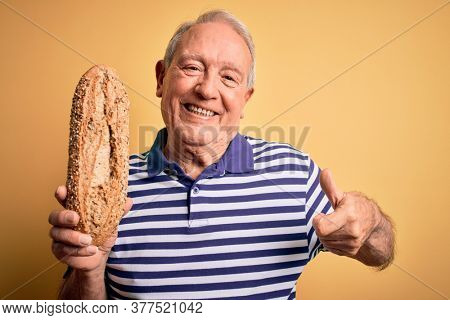 Grey haired senior man holding healthy wholemeal bread over yellow isolated background happy with big smile doing ok sign, thumb up with fingers, excellent sign