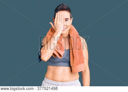 Young woman with short hair wearing sportswear and towel using smartphone covering one eye with hand, confident smile on face and surprise emotion.