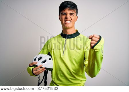 Young handsome cyclist man holding security bike helmet over isolated white background annoyed and frustrated shouting with anger, crazy and yelling with raised hand, anger concept