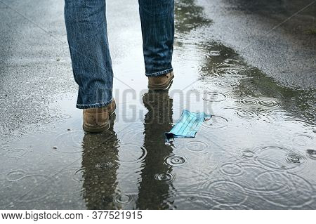 Medical Face Mask Discarded On The Asphalt In The Rain, Man Walks Away, Thoughtless Against The Dang