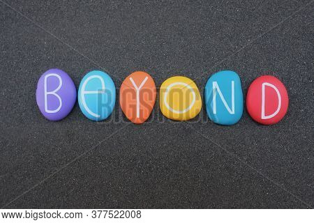 Beyond, English Word Composed With Multicolored Stone Letters Over Black Volcanic Sand