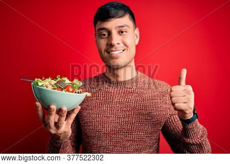 Young hispanic man eating vegetarian healthy salad over red isolated background happy with big smile doing ok sign, thumb up with fingers, excellent sign