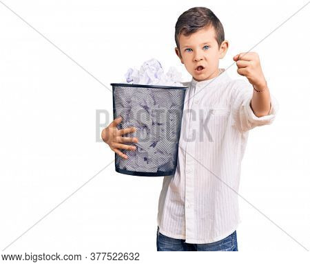 Cute blond kid holding paper bin full of crumpled papers annoyed and frustrated shouting with anger, yelling crazy with anger and hand raised