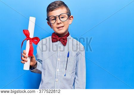 Cute blond kid wearing nerd bow tie and glasses holding diploma looking positive and happy standing and smiling with a confident smile showing teeth