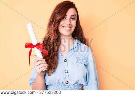 Young beautiful woman holding graduate degree diploma looking positive and happy standing and smiling with a confident smile showing teeth