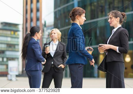 Female Office Colleagues With Takeaway Paper Cups Standing Outdoors, Drinking Coffee, Talking, Discu