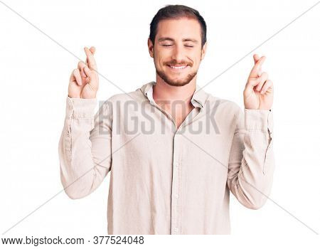 Young handsome caucasian man wearing casual clothes gesturing finger crossed smiling with hope and eyes closed. luck and superstitious concept.