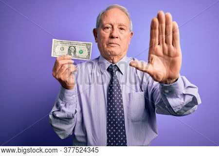 Senior grey haired man holding one dollar bank note over purple background with open hand doing stop sign with serious and confident expression, defense gesture
