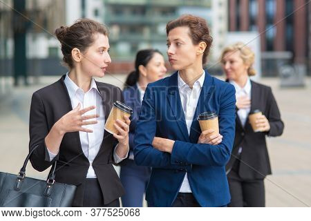 Female Business Colleagues With Takeaway Coffee Mugs Walking Together In City, Talking, Discussing P