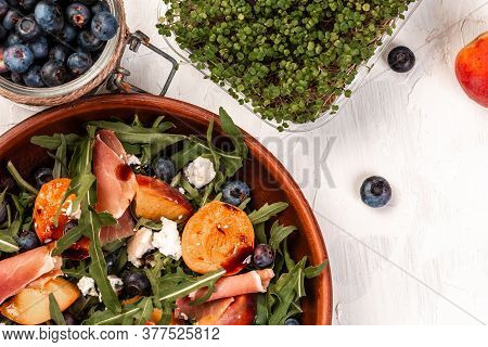 Delicious Salad With Grilled Peaches, Prosciutto And Cheese, Snack On A Light Background, Top View.