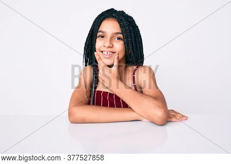 Young african american girl child with braids wearing casual clothes sitting on the table looking confident at the camera smiling with crossed arms and hand raised on chin. thinking positive.