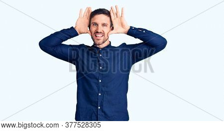 Young handsome man wearing casual shirt smiling cheerful playing peek a boo with hands showing face. surprised and exited