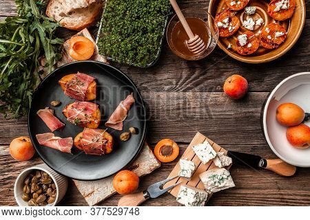 Tasty Snack With Cheese, Peach, Prosciutto Slices And Capers, Microgreen,on Wooden Table, View From