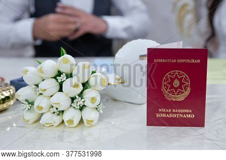 Marriage Certificate . White Tulips . In The Background, The Groom Fixes The Ring On His Hand . Marr