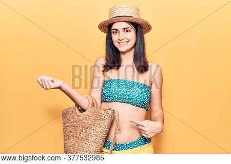 Young beautiful girl wearing bikini and hat holding bag smiling happy pointing with hand and finger