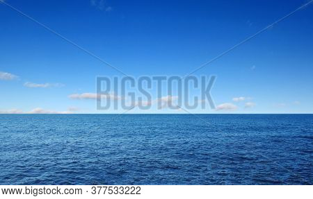 Blue sea with waves and cloudy blue sky