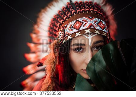Beautiful Young American Indian Woman With Make Up In Traditional Feather Hat And Clothes Holds A La