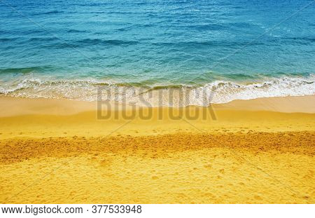 Wave of blue ocean on sandy beach.