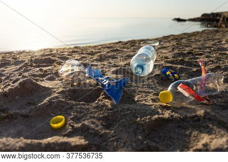 Oceans Pollution. Polluted Beach With Plastic Trash And Single-use Bottles Lying On Sand Near Sea Ou