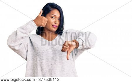 Hispanic woman with long hair wearing casual clothes doing thumbs up and down, disagreement and agreement expression. crazy conflict