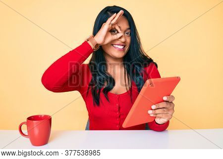 Beautiful latin young woman with long hair using touchpad sitting on the table smiling happy doing ok sign with hand on eye looking through fingers