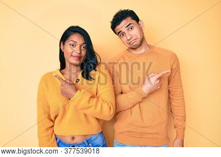 Beautiful latin young couple wearing casual clothes together pointing to both sides with fingers, different direction disagree