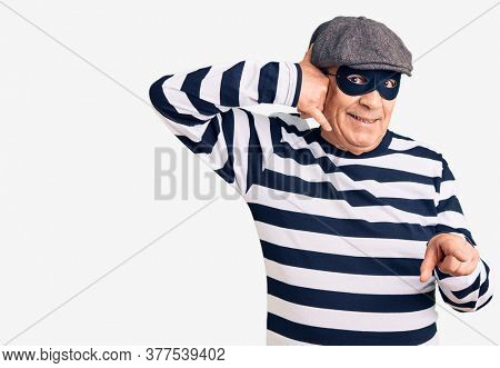 Senior handsome man wearing burglar mask and t-shirt smiling doing talking on the telephone gesture and pointing to you. call me.