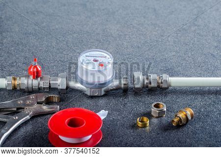 Plumbing Tools And Plumbing Line On Gray Surface With Copy Space. Installation Water Meter.